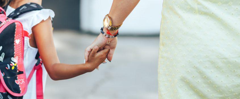 en vårdnadshavare håller ett barn i handen.