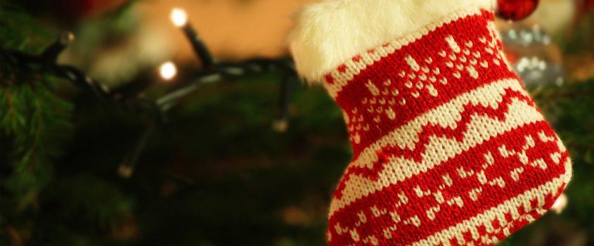 En stickad julstrumpa hängandes i en gran.