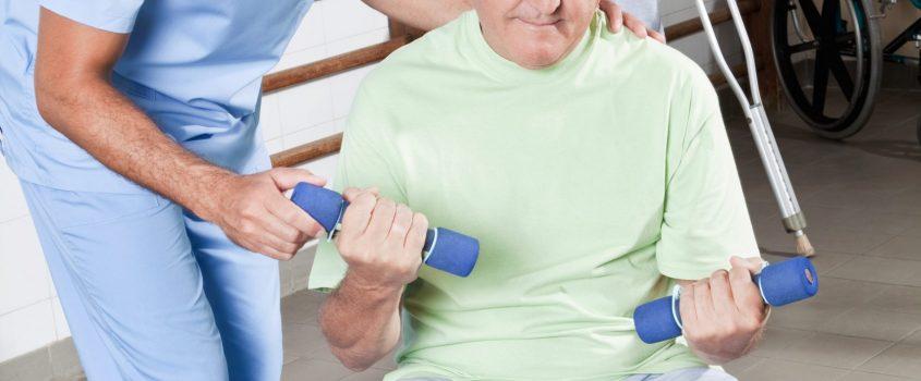 Sjukgymnast hjälper manlig patient som håller hantlar och sitter på en gymboll.