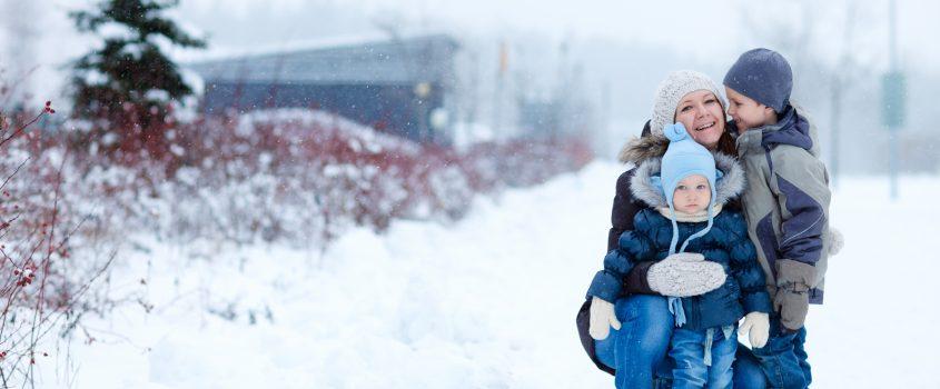 Kvinna står på huk och kramar om två barn. Det yngre barnet står framför henne och det äldre barnet står i profil och ler mot kvinnan. Det är vinter och snö på backen.