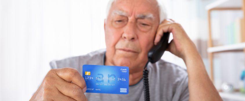 Äldre man sitter i telefonsamtal och håller i sitt kreditkort framför sig.