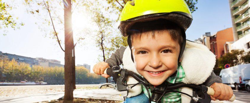 Pojke på cykel med cykelhjälm som skrattar
