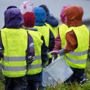 Barn i gula västar med hinkar som plockar upp skräp