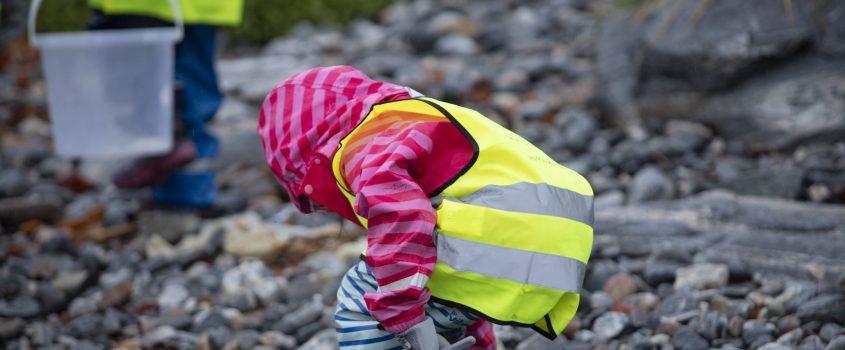 Barn i reflexvästar och med hinkar plockar upp skräp på en strand