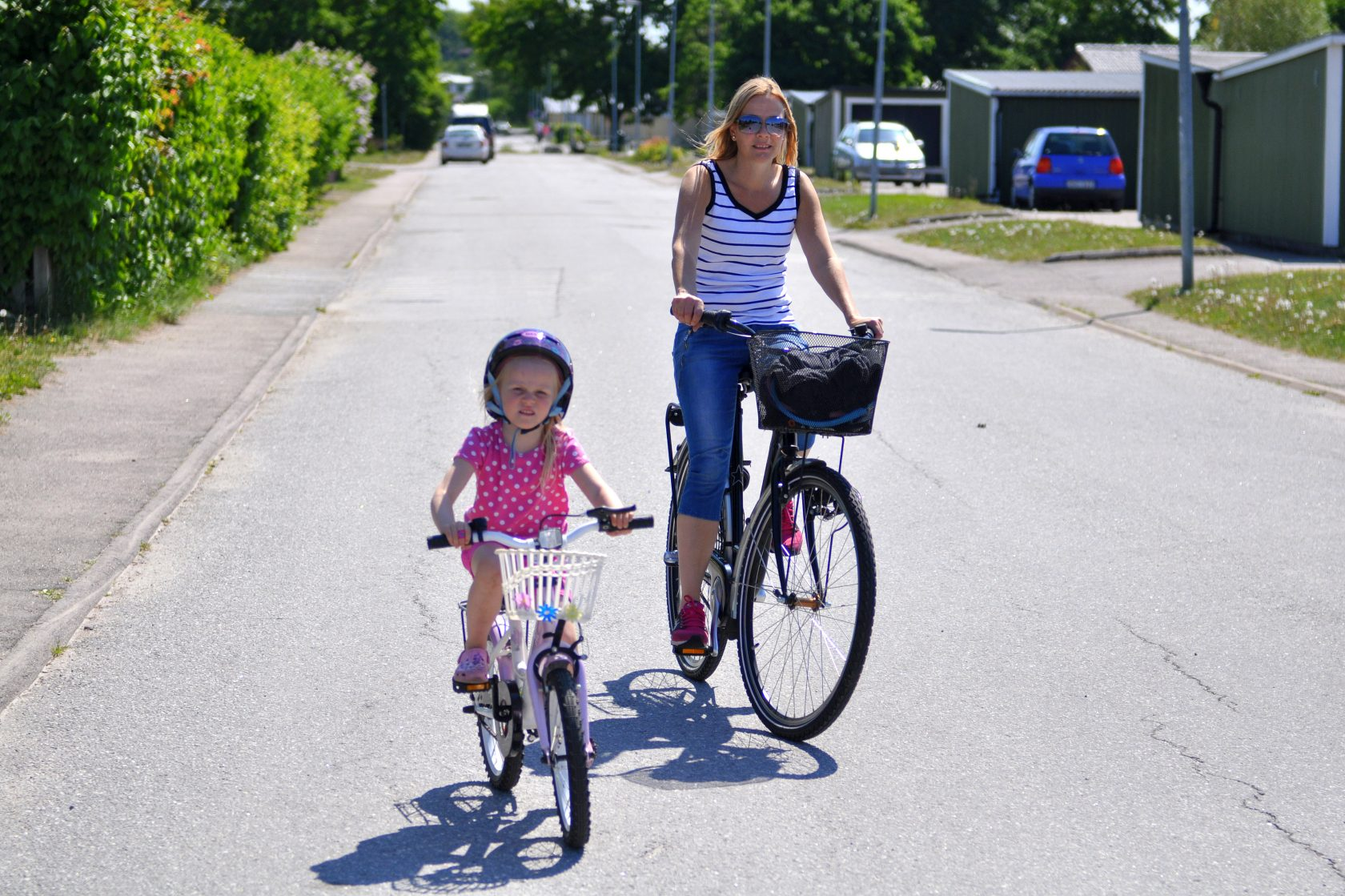 Vuxen och barn på varsin cykel i ett villaområde