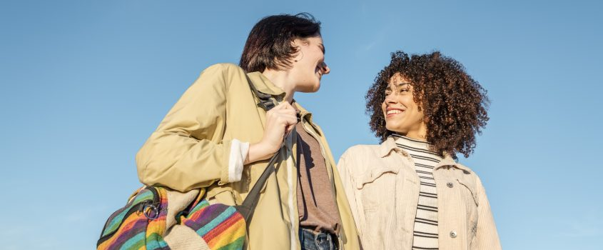 Två kvinnor som tittar på varandra och ler. En klarblå himmel syns i bakgrunden av dem.