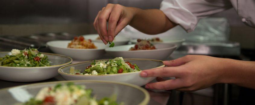 En kock som förbereder flera tallrikar med nyttig, näringsrik och god mat